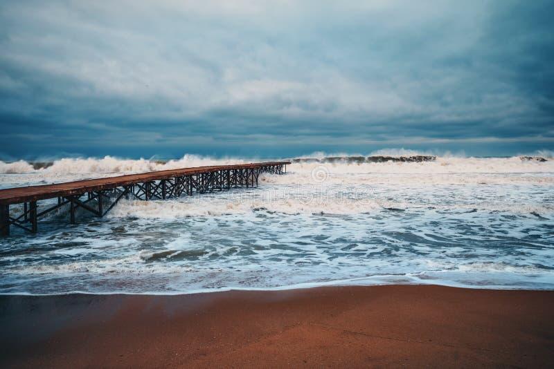 Old broken bridge in the sea and huge waves in the deep sea stock photos