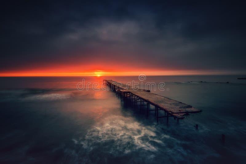 Old broken bridge in the sea, long exposure stock photos