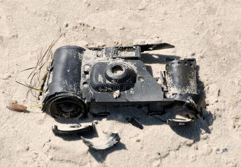 Old broken camera. In the sand on the beach stock images