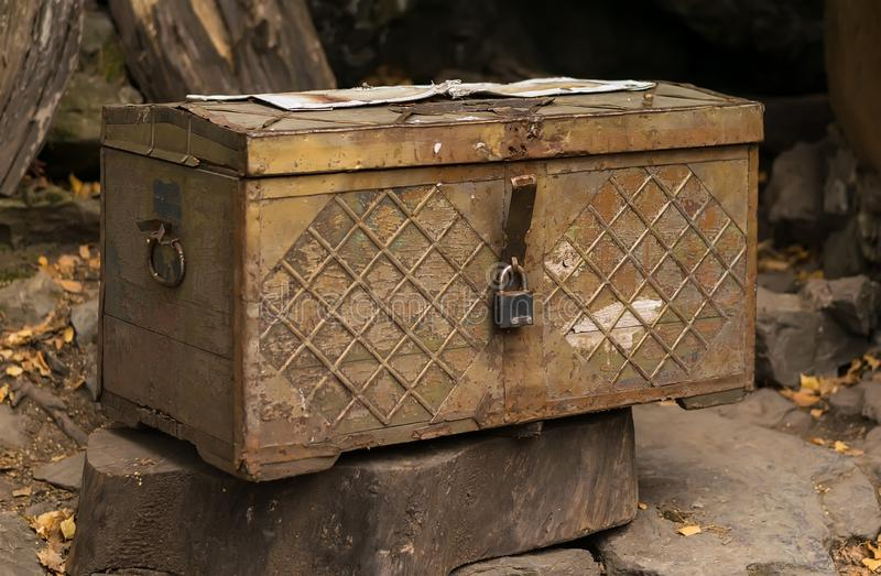 An old chest with a lock stands on a tree stump stock image