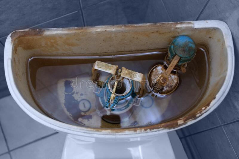 Old broken fittings in dirty toilet bowl. View from above stock image