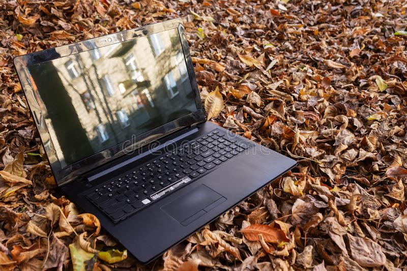 Broken laptop thrown out on the street like garbage royalty free stock photo