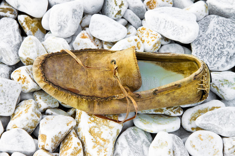 Old broken moccasin abandoned on white gravel stock photography