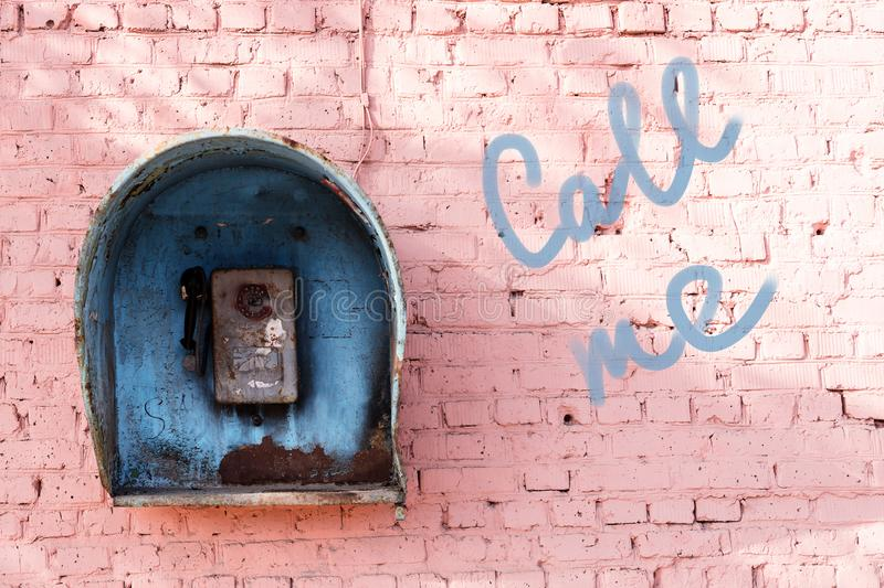 Old broken phone of the Soviet period on the pink brick wall of the house and the inscription: call me. Blue phone booth stock photo