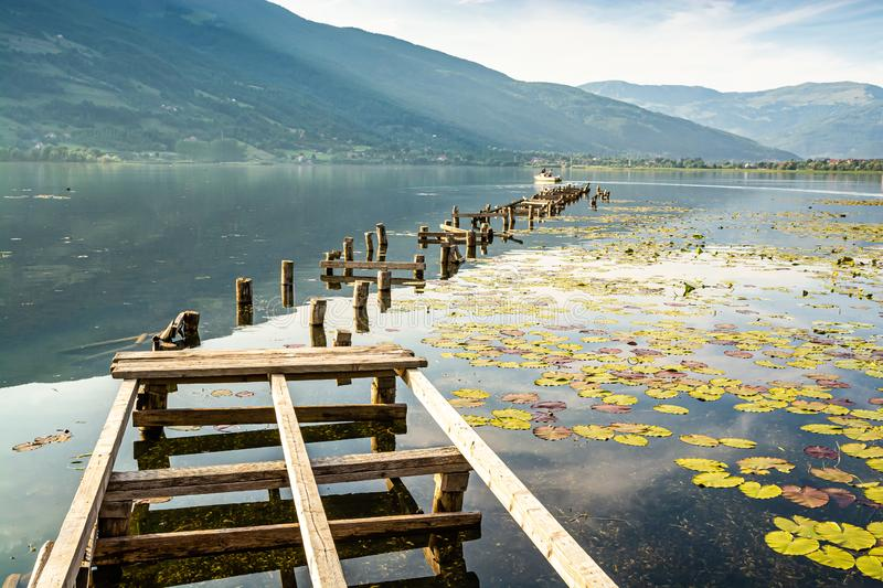 Old broken pier with boat on Plavsko lake between water lilies, Montenegro, Europe.  royalty free stock photography