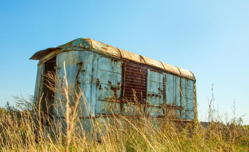 Old broken rusty van, camper, thrown on the field. Summer day. Old rusty van, camper, thrown on the field. Summer day, field and sky stock photography