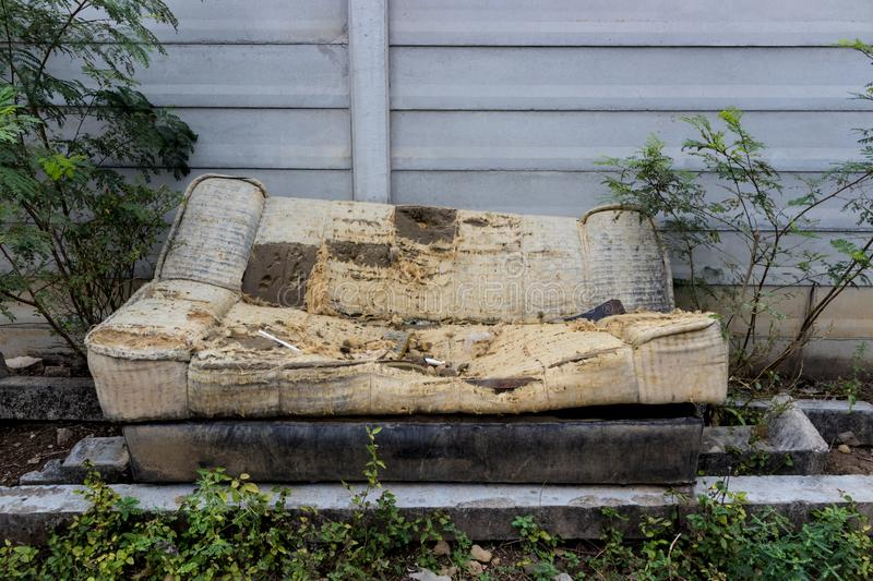 old and broken sofa left on the side of street stock image