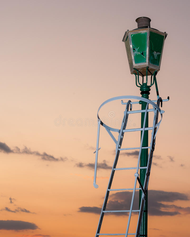 Old broken street lamp that does not work. Shot in sunset royalty free stock image