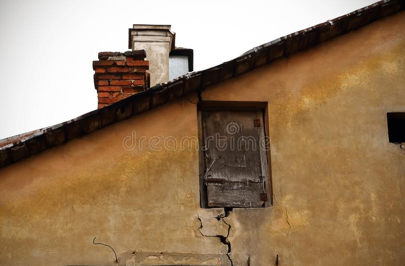 Old broken tiny wooden brown door near the roof top of aged old town building royalty free stock image