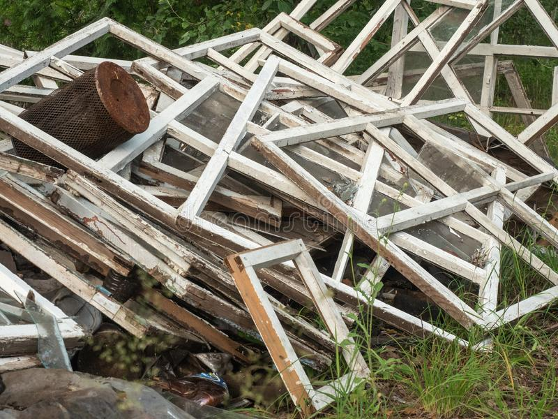 An old broken window frames piled together on green grass. A lot of wooden window casements with blistered up white stock photo
