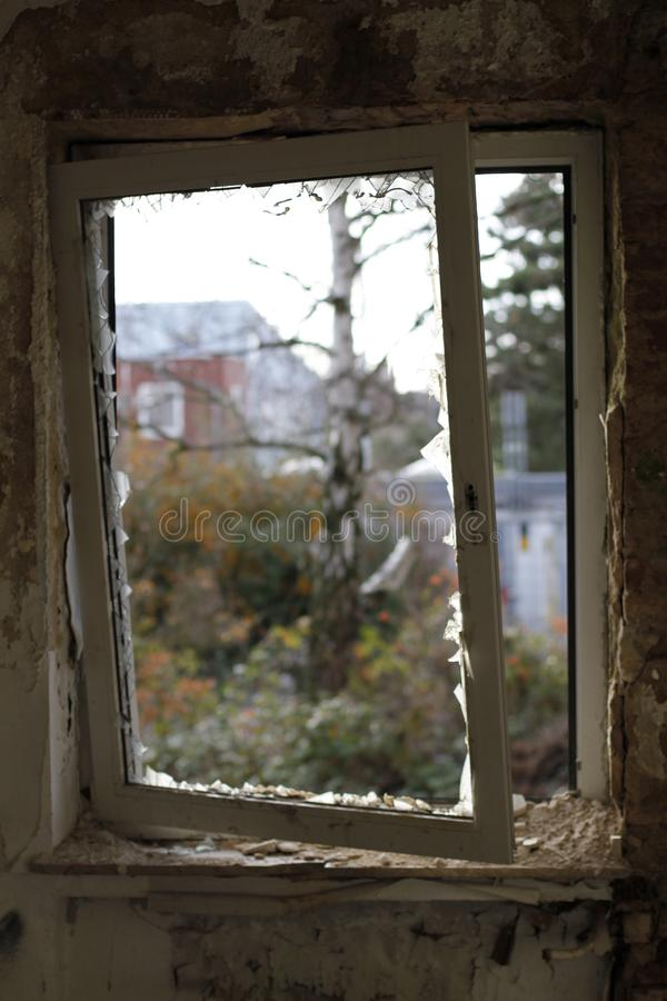 Old broken window with a view to the outside stock photo