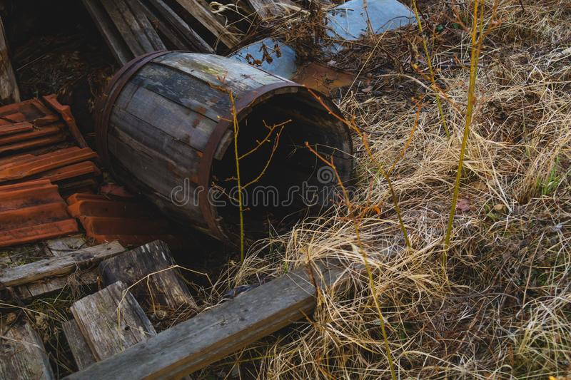 Old broken wooden barrel in the yard. Old broken wooden barrel laying in the yard, background, brown, retro, vintage, twigs, dry, iron, oak, ancient, alcohol stock photos