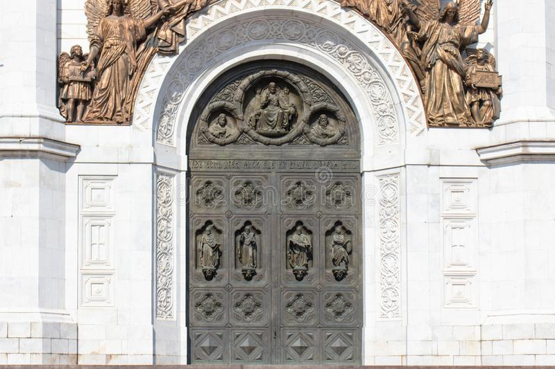 Old bronze door in the temple. The high gates of the temple, the arch on top of the bronze figures of angels. stock images