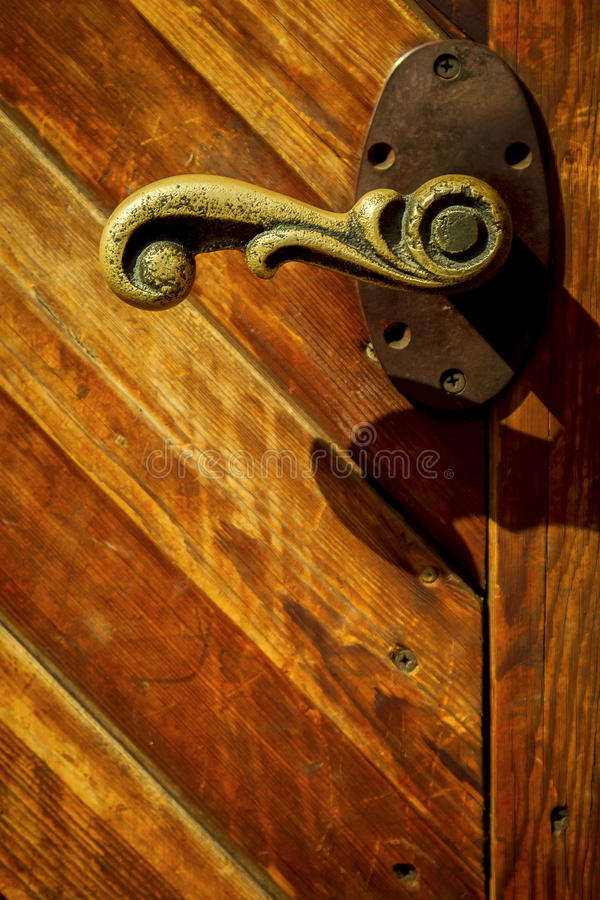 Old bronze handle on the wooden gate royalty free stock image