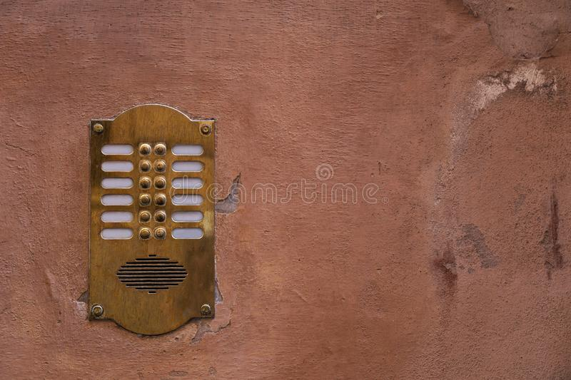 Old bronze intercom on an old wall with peeling paint. Vintage background royalty free stock photos