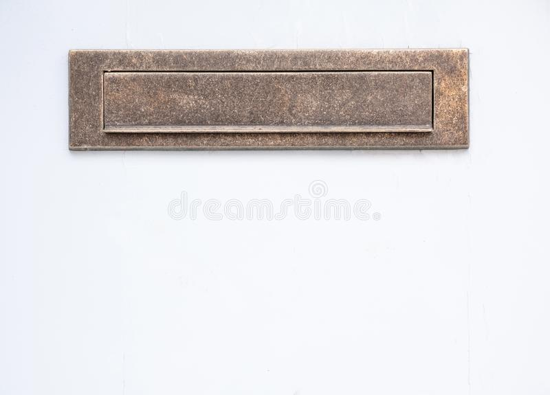 Brass mail letter box on white color wall background. Closeup view with details royalty free stock photo
