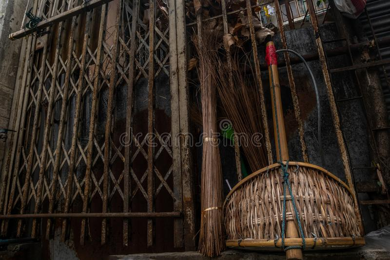 Old broomstick and collects garbage in scoop on the road, near to the old steel frame door. sanitation worker sweep street stock photos