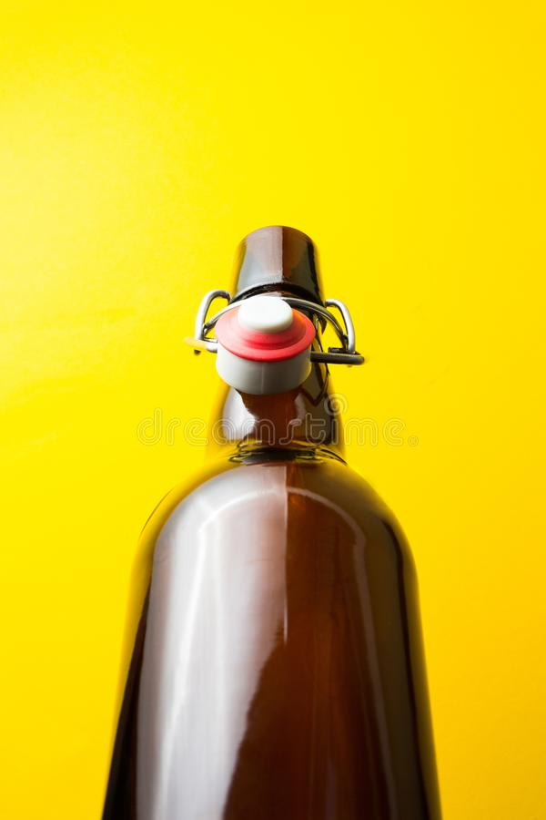Old brown bottle with beer without a label on a yellow background royalty free stock photography