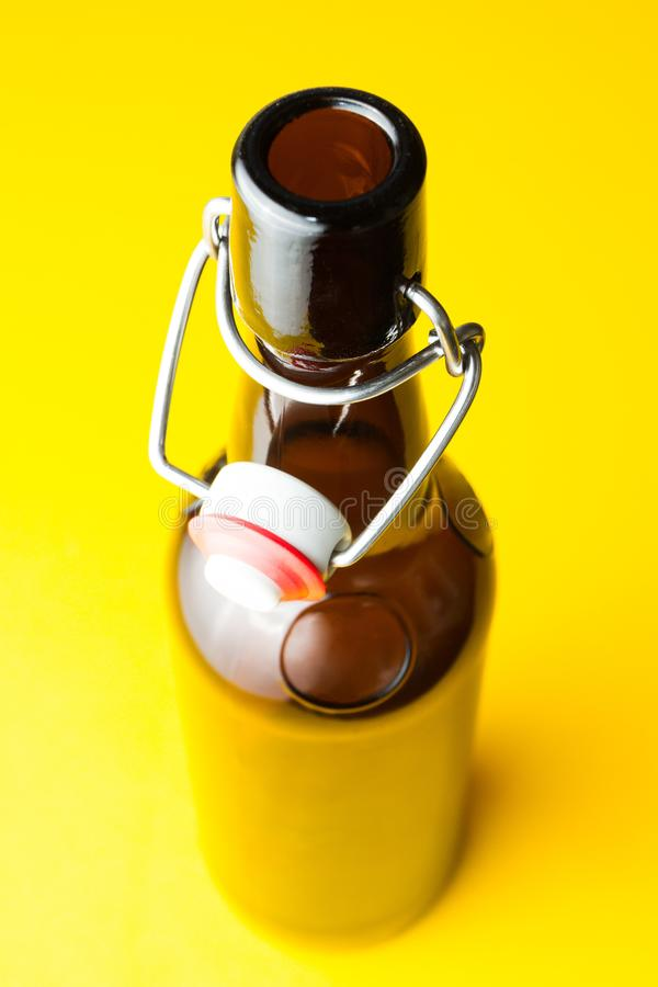 Old brown bottle with beer without a label on a yellow background royalty free stock photos