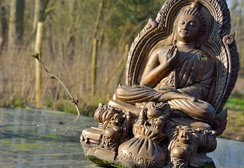 Old brown Buddha statue. On a table in the sun royalty free stock images