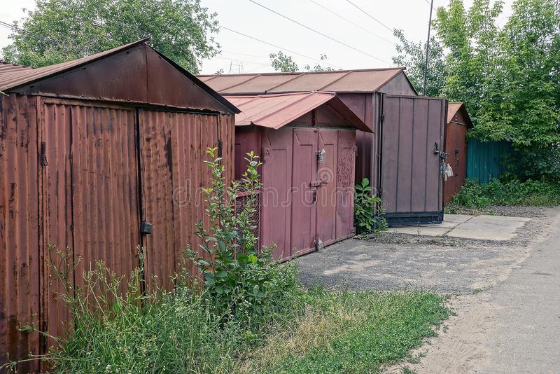 Old brown iron garages in the thickets of grass near the road royalty free stock image