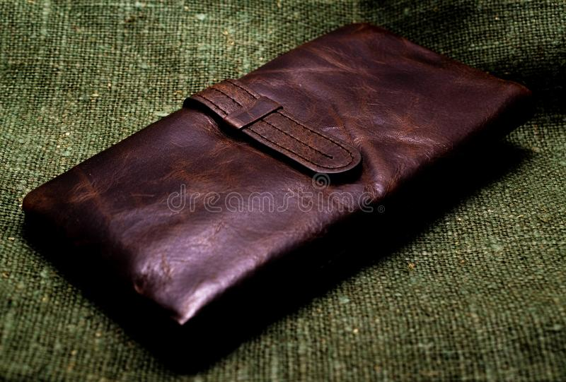 Old brown leather wallet on a green burlap background. Close-up.  stock photo