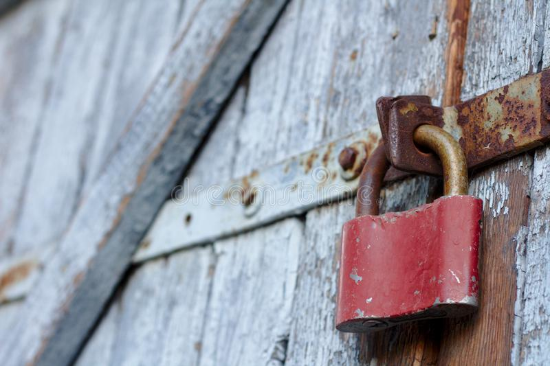 Old brown padlock on a gray door with wooden planks of cracked paint and rust. Vintage gates with metal stripes and bolts royalty free stock photos