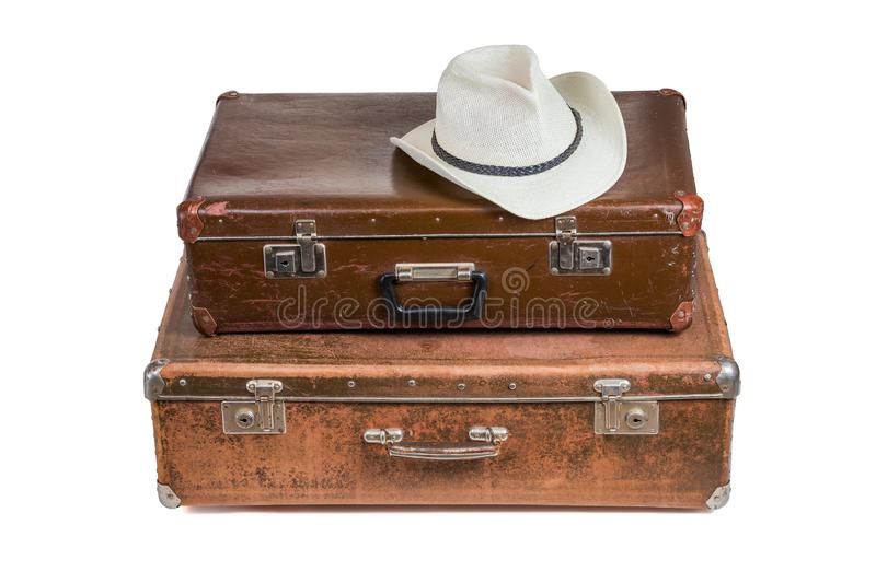 Old brown soviet fiber suitcases one on top of other with white summer hat isolated on white background royalty free stock photography