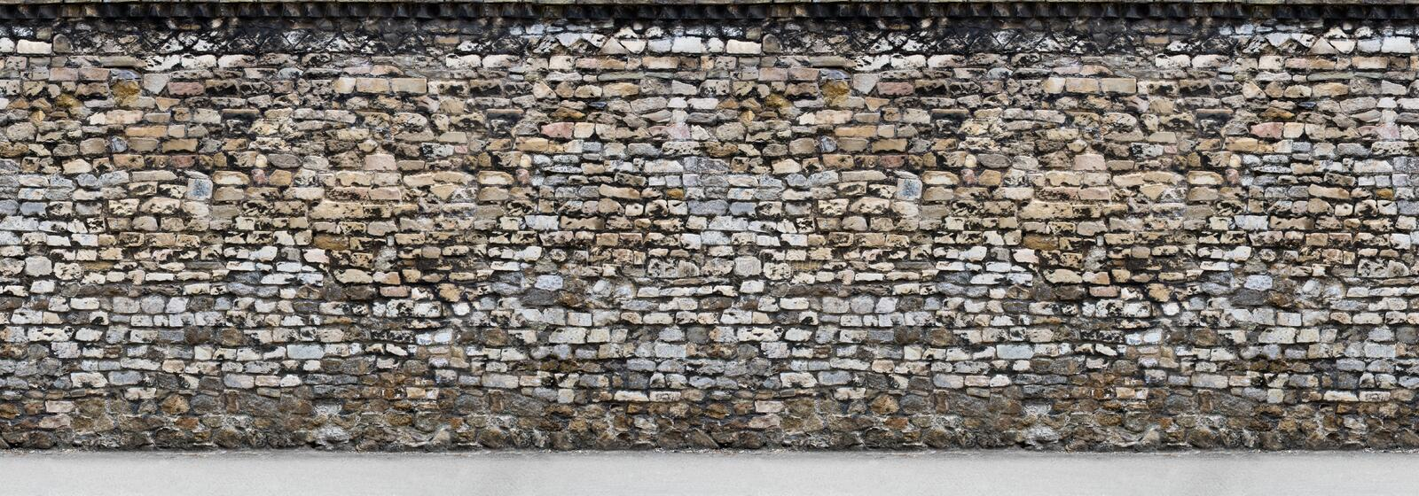 Old brown stone wall with part of the road Horizontal Seamless royalty free stock image