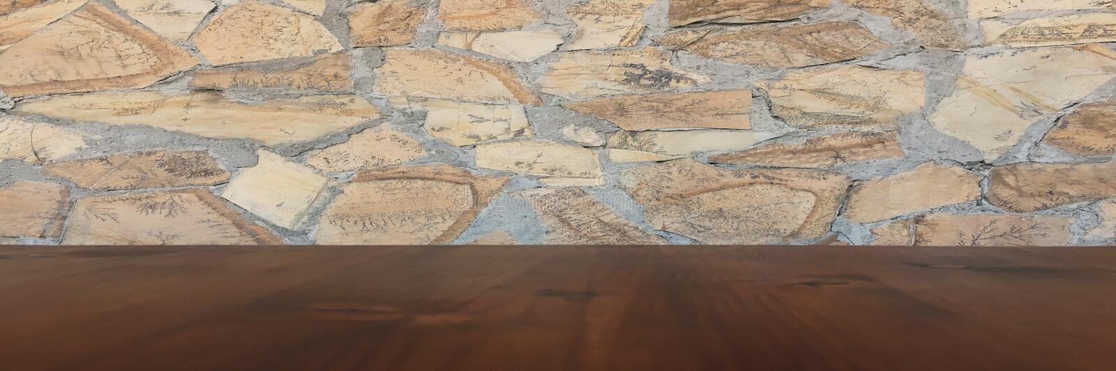 Old brown wood table with blurred stone block wall in light room background. stock image
