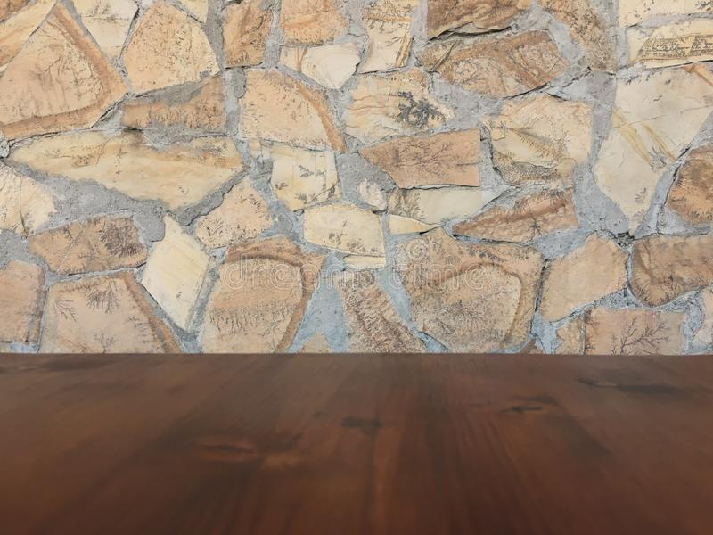 Old brown wood table with blurred stone block wall in light room background stock image