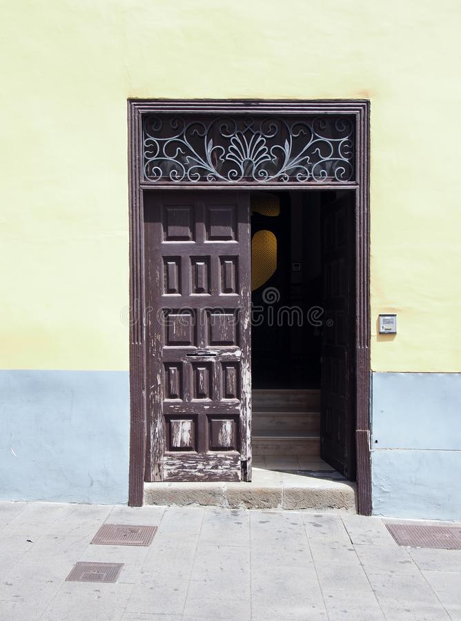 Old brown wooden door with panels in a traditional spanish house. Half open revealing stairs inside decorative iron panel and yellow painted walls in bright stock images