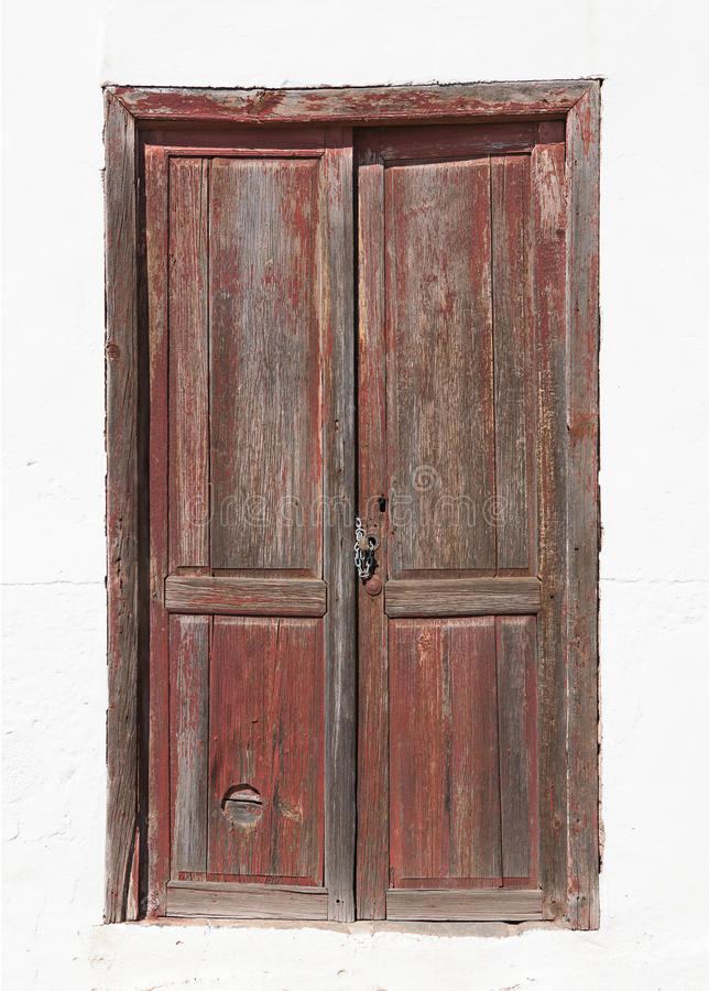 Old brown wooden door in a white facade. Old brown wooden door in a newly painted facade of a house on La Gomera, Canary Islands, Spain stock image