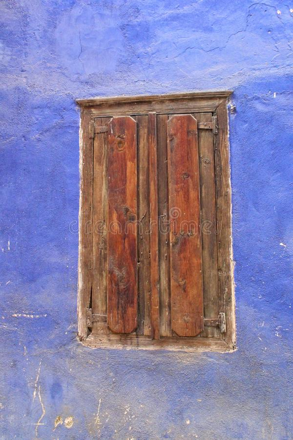 An old brown wooden window with blue wall. Old brown wooden window withh blue wall concrete texture abstract house ancienr ancient historicak historical history royalty free stock photo