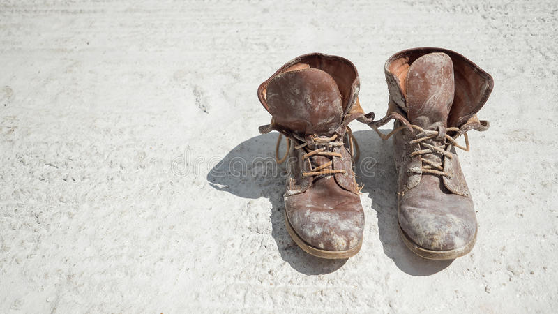 Old brown work boots covered in concrete. Worn by a woman stock photos