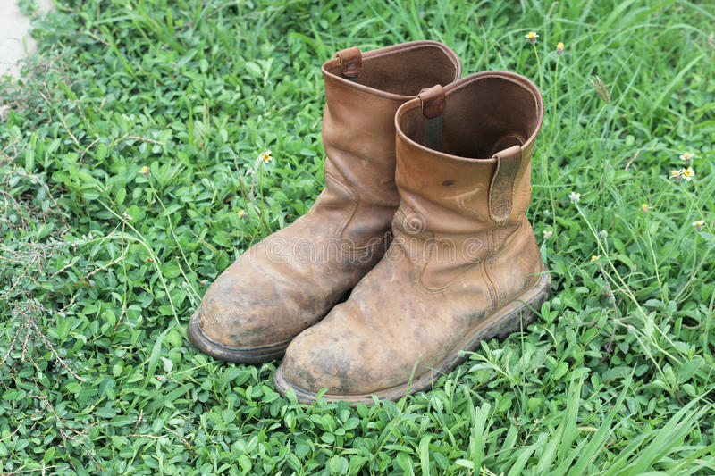 Old brown work boots. On green grass royalty free stock photo