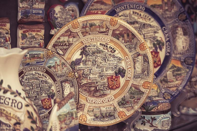 Old Budva, Montenegro - July 19, 2019: Colorful painted plates and spoons showing the map of Montenegro at a souvenir stall in the royalty free stock image
