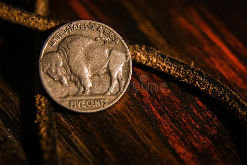 A buffelo nickel on wood and leather stock photo
