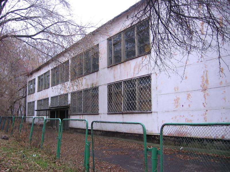 The old building of an abandoned school behind a fallen fence emptied in the fall idle stock image
