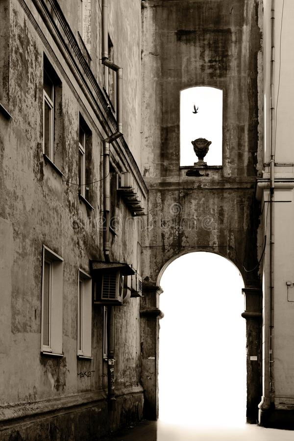 Old building with an arch and a flying bird, monochrome. royalty free stock photos