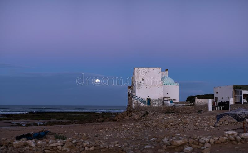 Old building at coast of Sidi Kaouki, Morocco, Africa. Moon in the evening sky. Sunset time. morocco`s wonderfull surf to royalty free stock photography