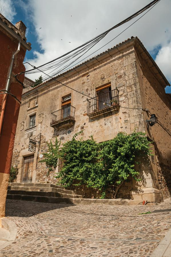 Old building facade with green creeper, on corner of narrow alley at Caceres stock photo