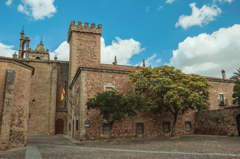 Old building and flowered tree in front of cobblestone square at Caceres stock image