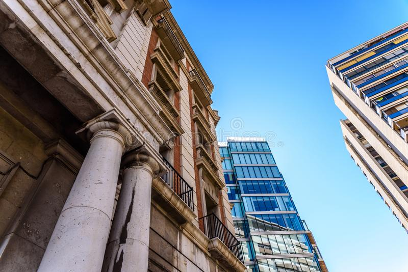 Old building in the foreground in front of modern business office buildings with large glass windows, blue sky background royalty free stock photos