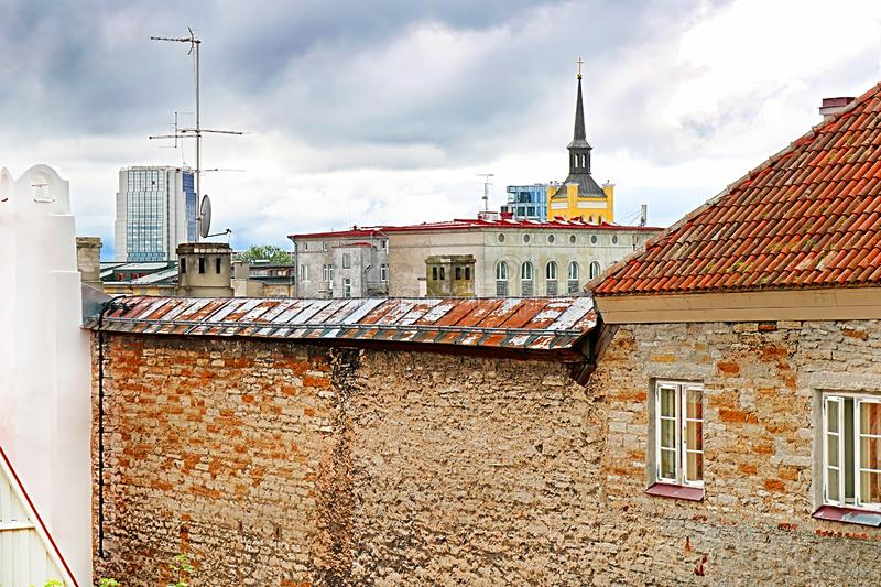 Old building in the foreground and morden buildings on the background in Tallinn, Estonia stock image