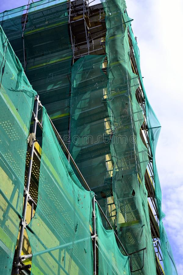 Old building in reconstruction, scaffolding around school royalty free stock photo