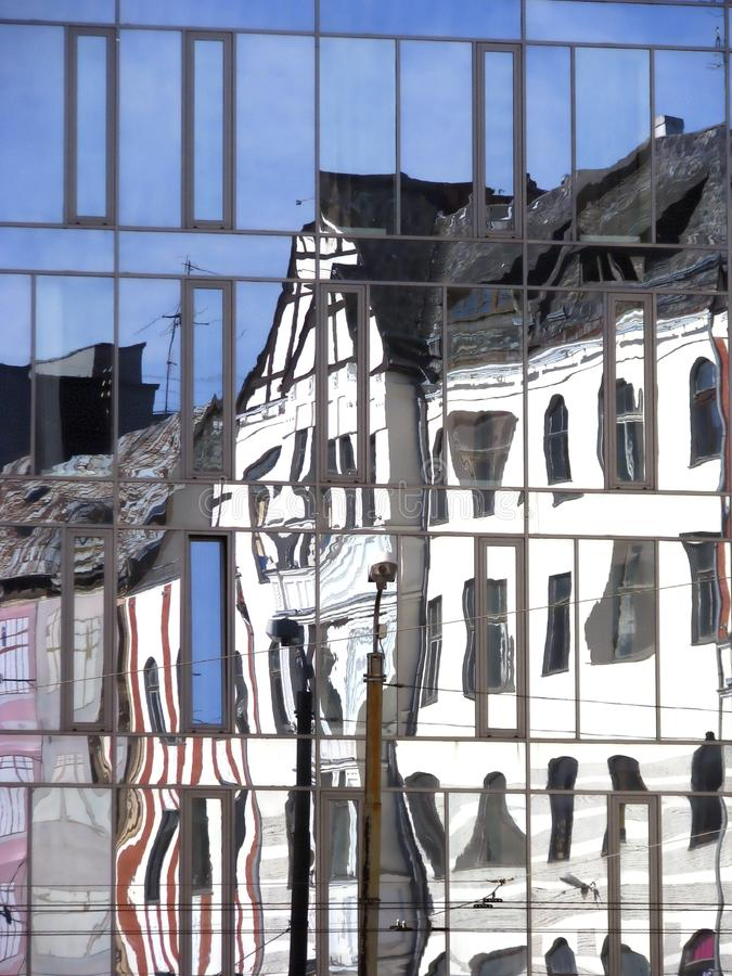 Old building is reflected in the glass windows of. Modern building stock images