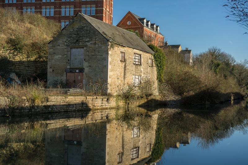 Old building reflecting on water in the restored Stroudwater Canal in Stroud. Gloucestershire, UK royalty free stock photos