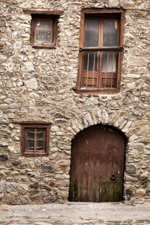 Old building rocks and stones maded. Wooden door and windows crooked stock images