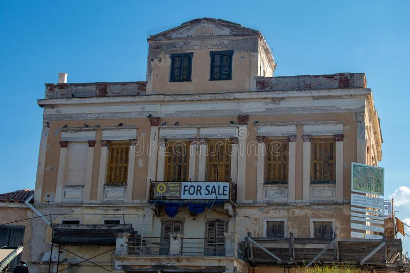 An Old Building for Sale on the Greek Isle of Aegina. An old building for sale along the main street in the port of Aegina on the Greek Island of Aegina royalty free stock images